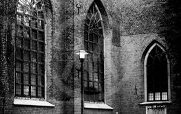 A single street light next to an old church in black and...