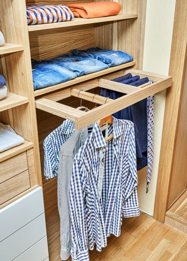 Modern wardrobe with clothes hanging on slide out racks...