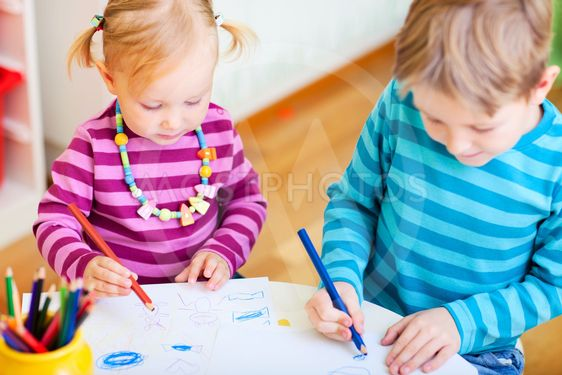 Brother and sister drawing in their room