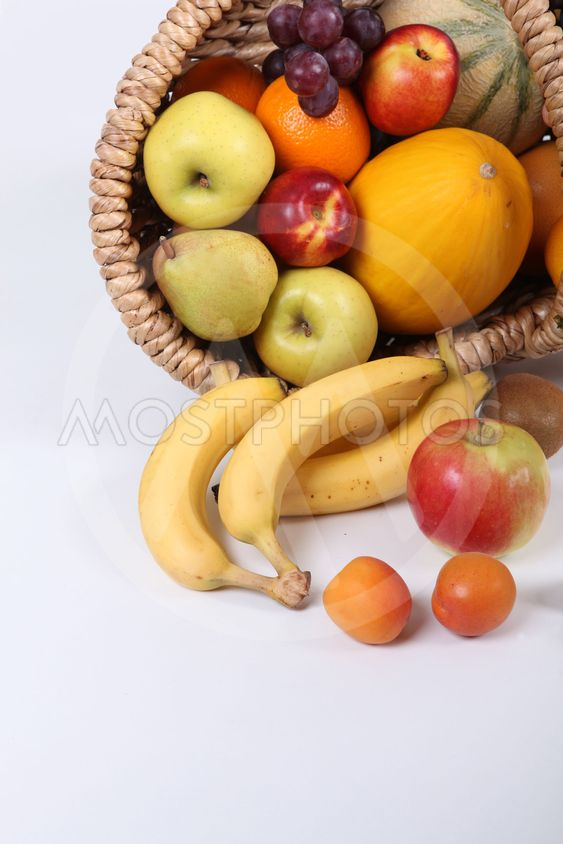 Wicker basket overflowing with fresh shiny fruit
