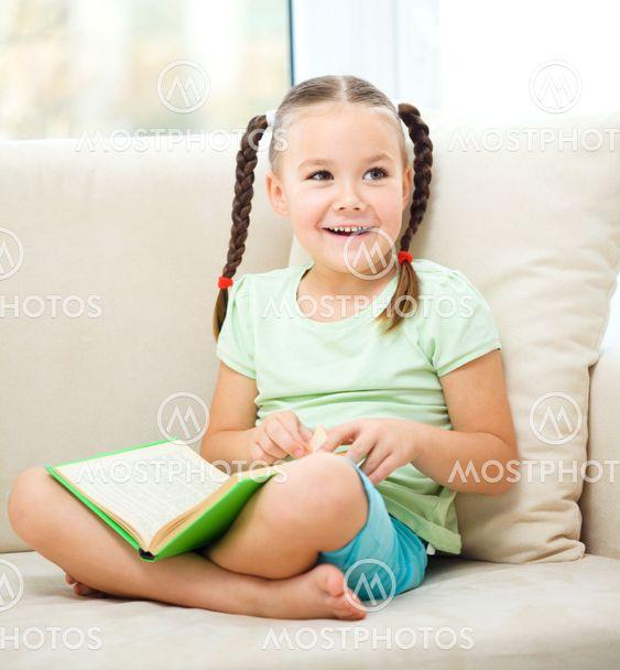 Lille pige læser en bog