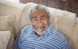 Smiling senior man sitting on sofa in living room