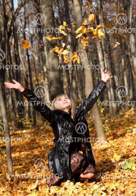 vacker flicka kastar upp hösten lämnar