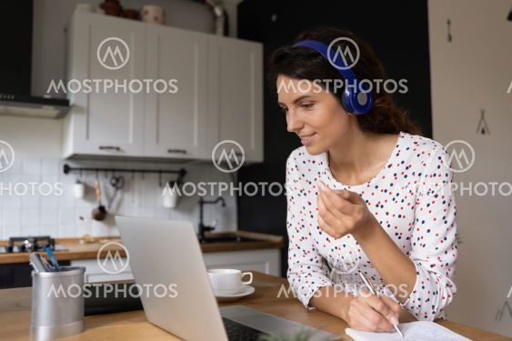 Smiling woman watch webinar on laptop at home