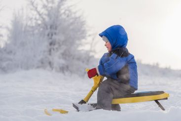 little child riding a snow scooter in winter