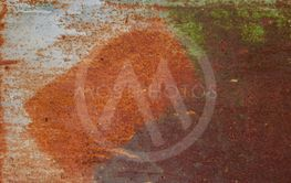 painted iron surface with a large rusty and metal...