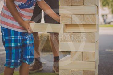 Kid playing a big jenga game