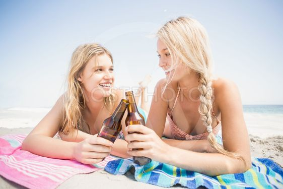 Happy women lying on the beach with beer bottle