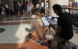 Street artist paints a portrait in Milan