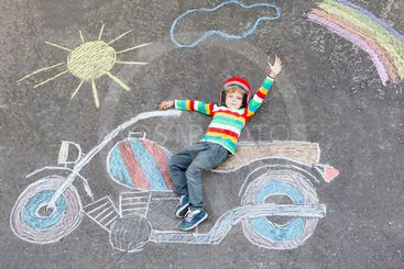 Little child in helmet with motorcycle picture drawing...