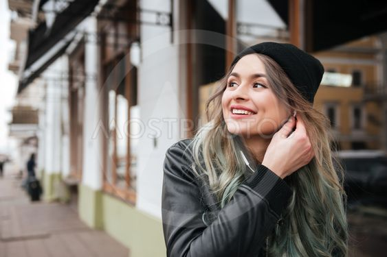 Gorgeous young woman wearing hat walking on the street