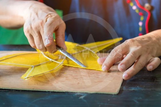 Eldery woman making and build star-shaped kite or thai...