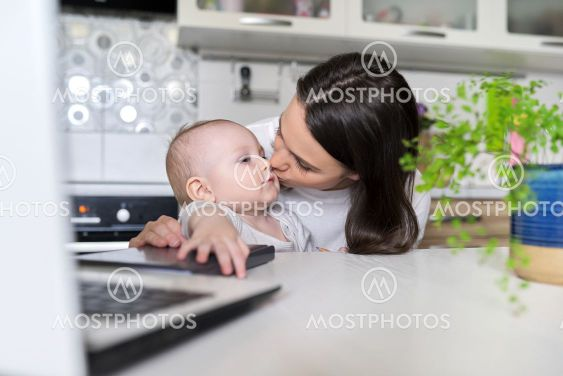 Portrait of mom and baby son sitting at home in kitchen,...