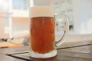 Cold fresh draft beer with beer foam in a large glass