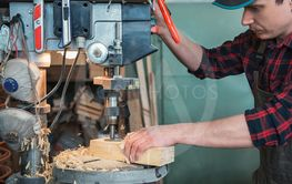 Carpenters with electric drill machine drilling wooden...
