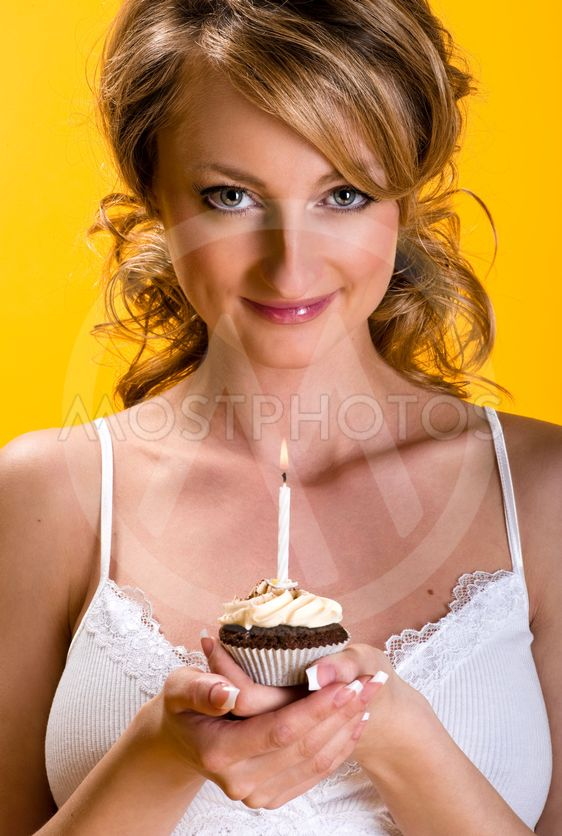 Beautiful young woman with birthday cake over yellow...