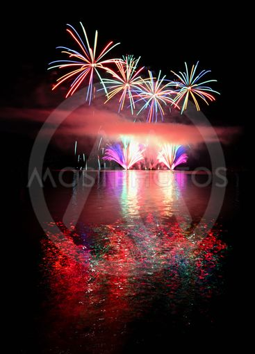 Beautiful colorful fireworks on the water surface. Night...