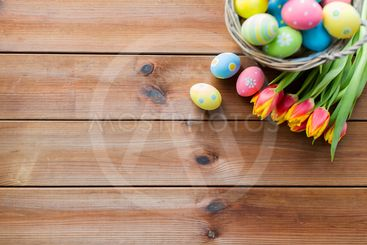 close up of easter eggs in basket and flowers