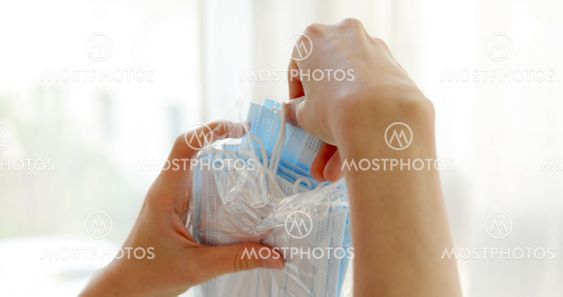 Crop woman taking out medical face mask from package in...