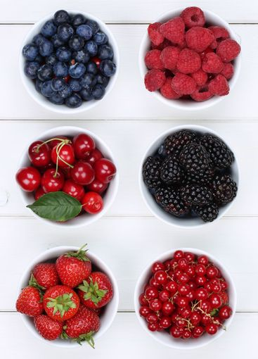 Berry fruits in bowls with strawberries, blueberries and...