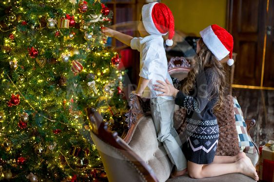 Boy and girl decorate the Christmas tree