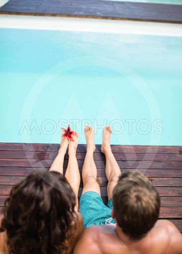 Young couple sitting by poolside