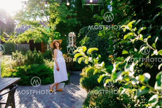 pregnant in white dress in back garden of house.