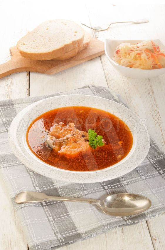 hungarian fish soup in a soup plate, salad and bread