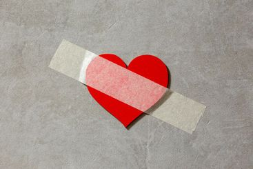 heart is taped to a concrete wall