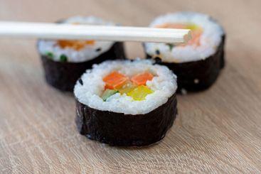 Three sushi rolls with chopsticks