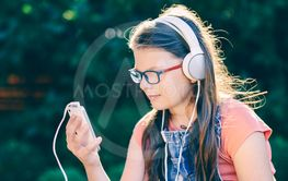 Teenager girl listening to music with headphones outdoors