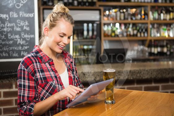 Pretty woman having a beer and looking at tablet