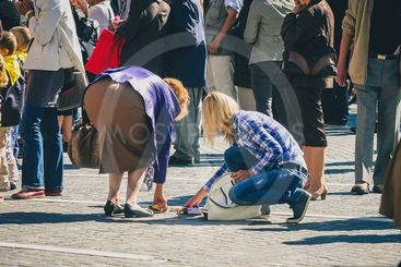 Woman picking contents of a purse in a crowd.