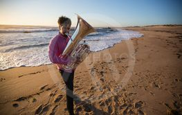 Man musician with a tuba playing on the ocean beach.