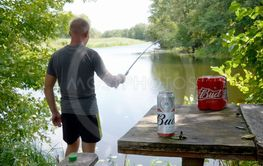 Budweiser Bud beer cans pack on old table and fisherman...