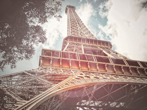 Eiffel tower from below with a sky with white clouds...