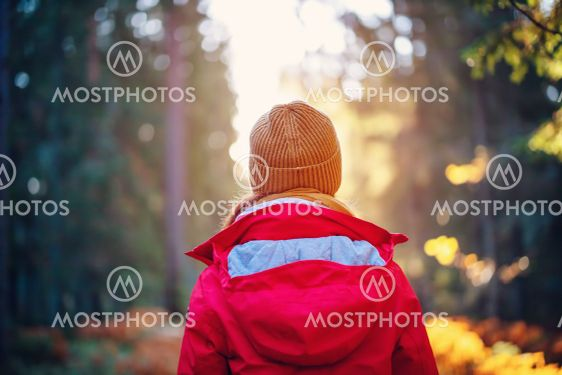 Young woman alone in the autumnal forest in sunrise.