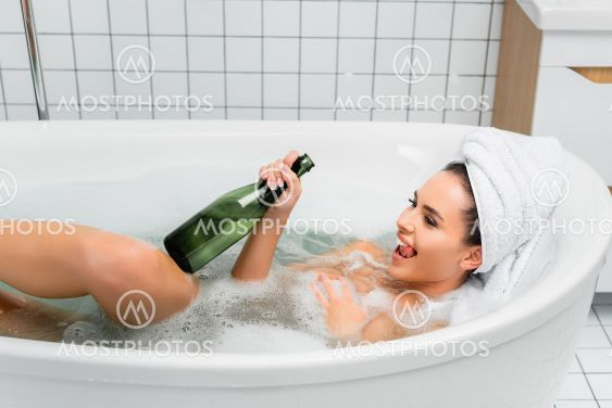 Cheerful woman with towel on head bathing with bottle of...