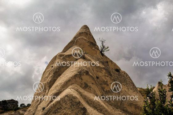 A strange spiky conical rock against a cloudy sky.