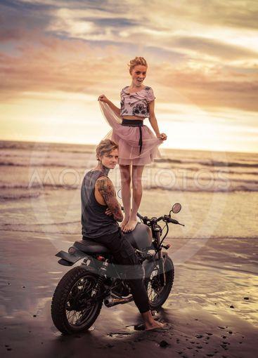 happy girlfriend standing on motorcycle near boyfriend on...