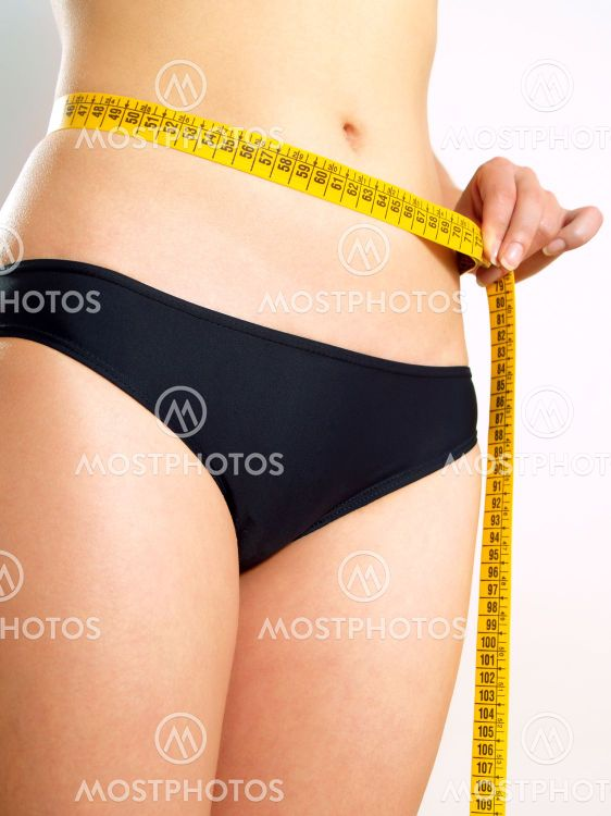 Girl measuring her abdomen after diet