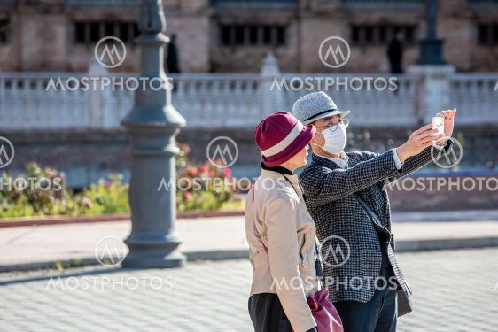 Couple in Seviille Spain taking selfie while one wears...