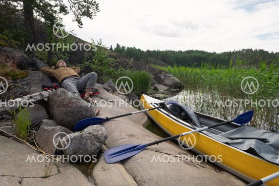 Man resting on the riverside after active paddling on...