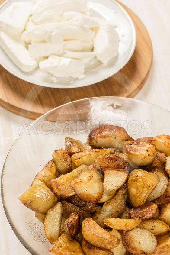 Fried young potatoes with cow cheese on the plate