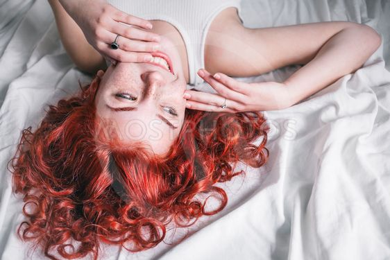 Portrait of young beautiful woman with long hair lying in...