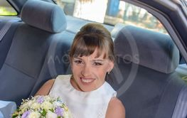 Pretty young bride in the back of the bridal car