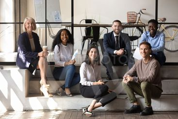 Happy diverse business team people sit on stairs in office