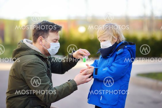 Mature man and little child wearing a protective mask...