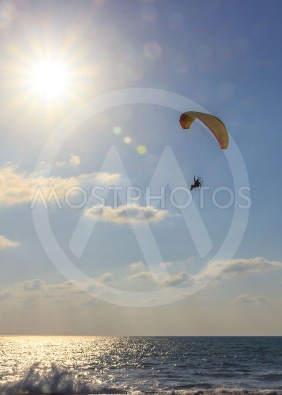 parachute jumper on motorized parachute flying over the...