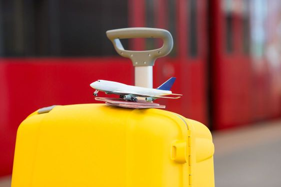 Closeup red passports and airplane small model on yellow...